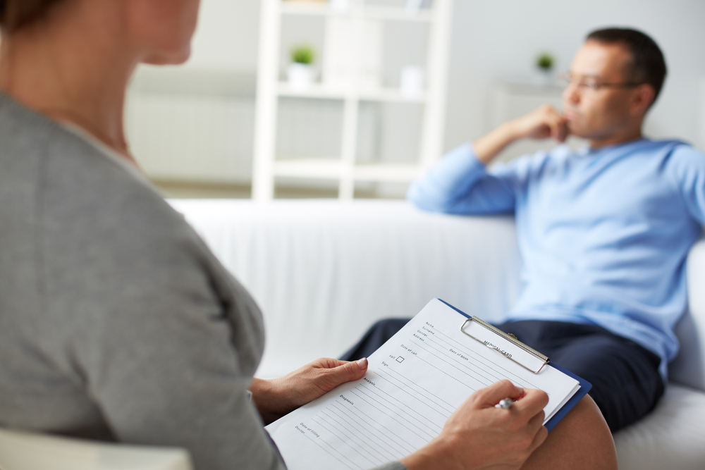 Therapist taking notes during therapy session with patient